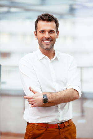 Happy casual businessman looking at camera against blurred background