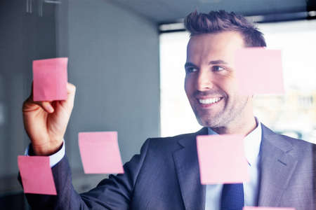 Young manager writing an idea on a sticky note