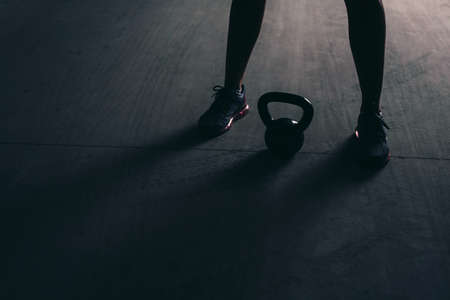 Legs of a bodybuilder with a kettlebell lying between them on a concrete floor Foto de archivo