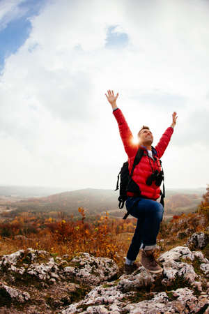 Happy hiker on the peak with his hands in the air