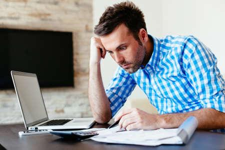 Shocked young man examining his surprisingly high bills