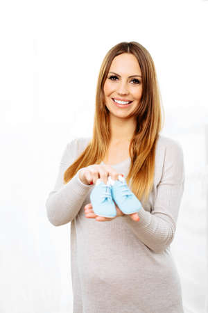 Happy pregnant woman holding a pair of baby shoes