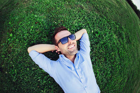 Portrait of a cheerful young man lying on the grass with his hands under the head