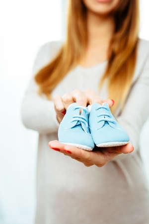 妊娠中の女性が持っている青いベビーブーツ 写真素材