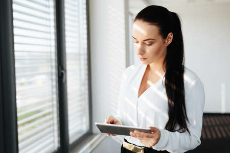 Female manager standing at a window and using her tablet to compare data