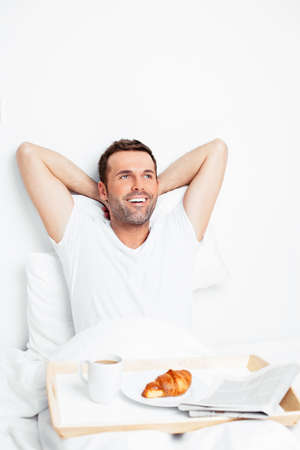 Attractive man relaxing in bed in the morning Stock Photo
