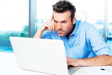 Young man looking at his laptop and surfing the web Stock Photo