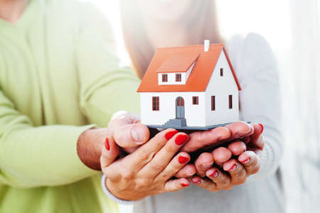 Man and a woman holding a minature house