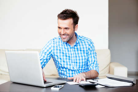 Handsome young man paying online using a laptop