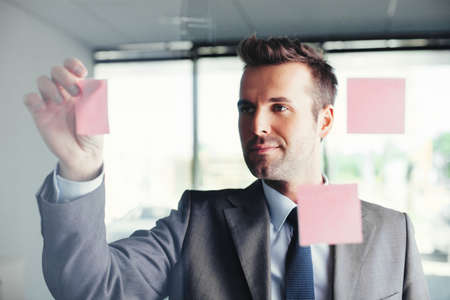 Young businessman sticking notes on a glass wall