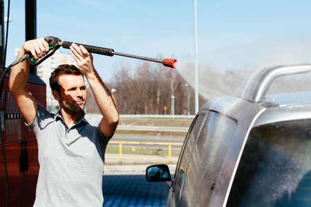 Young man washing his car at a jet car wash