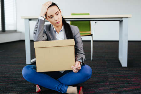 Photo of a worried woman who has been fired  sitting on the floor Stock Photo