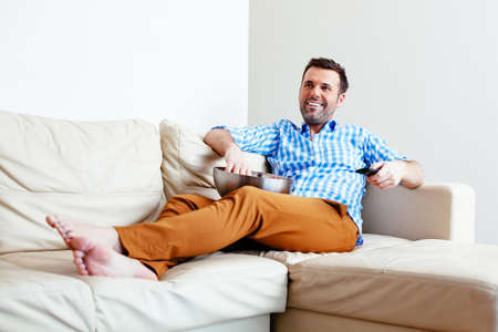 Handsome young man relaxing on a sofa with a bowl of popcorn Stock Photo