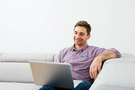 Relaxed man enjoying time with a laptop