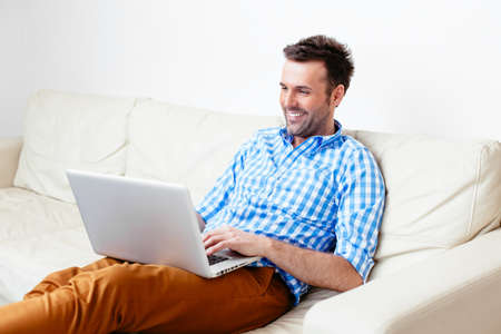 Happy handsome man sitting on a sofa and using his laptop