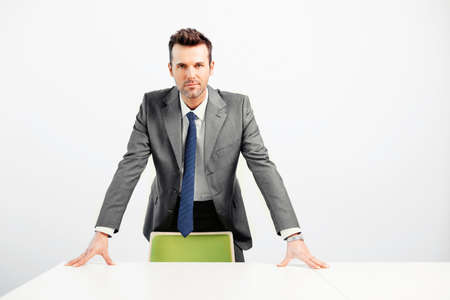 Confident young businessman standing at a table