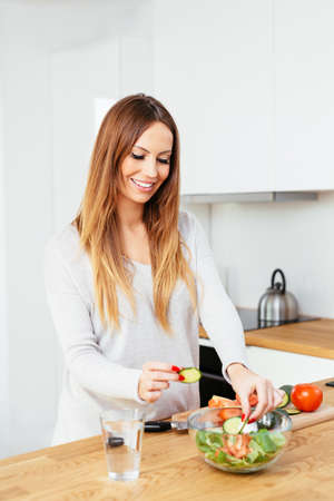 Smiling pregnant woman preparing a vegetable salad