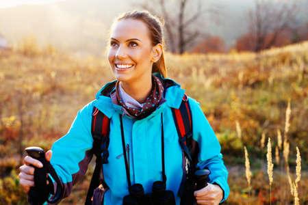 Jeune femme randonnée pendant l & # 39 ; automne avec des bâtons et sac à dos Banque d'images - 96556469