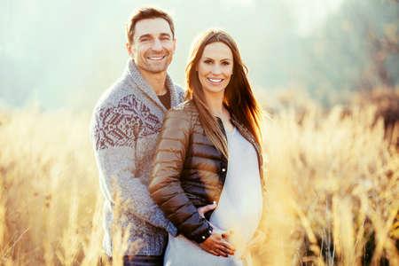 Happy young pregnant couple in nature Foto de archivo