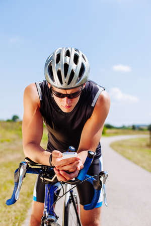 Triathlon cyclist navigating on his smartphone