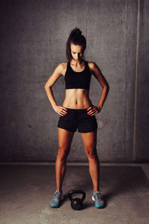 Female athlete against a concrete background looking at a kettlebell