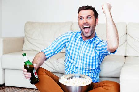 Joyful man enjoying the victory moment of his team on tv Stock Photo
