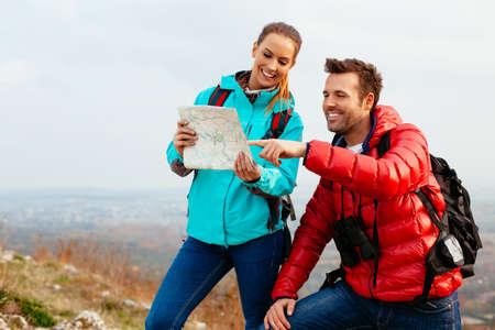 Happy couple reading map during autumn hiking. Foto de archivo