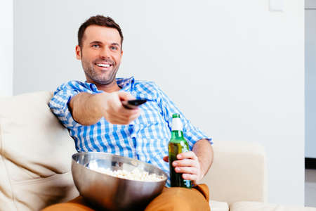 Handsome man watching TV with a beer and popcorn Stock Photo