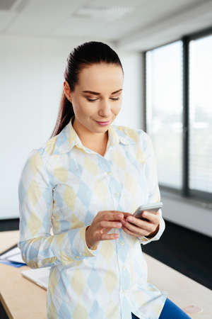 Photo of an attractive office worker sending an sms