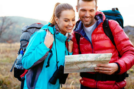 Young couple reading map during autumn backpacking, hiking.