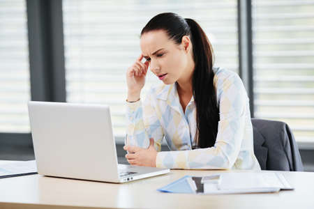 Photo of a an accountant looking at her laptop screen in confusion