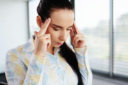 Female manager touching her head in a gesture of pain and deep thinking
