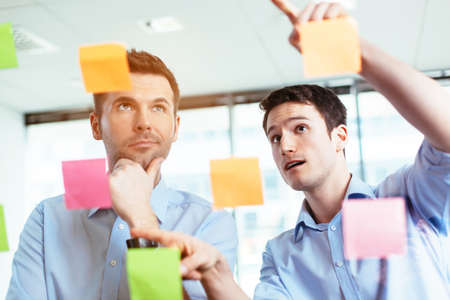 Two businessmen discussing ideas written on sticky notes Stock Photo