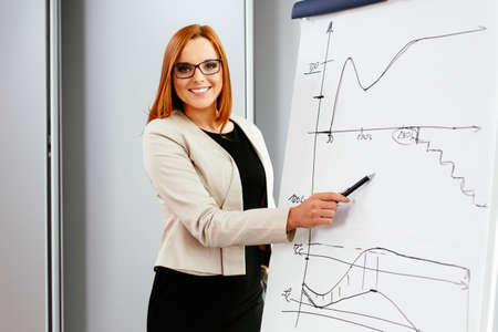 Young businesswoman pointing at a flipchart