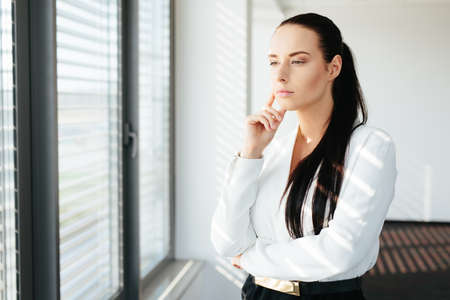 Portrait of an attractive female manager standing and thinking by a window Stock Photo