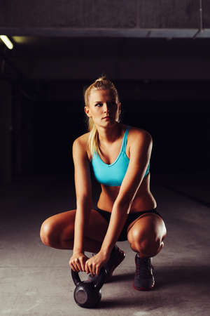 Blonde sportswoman crouching with a kettlebell in her hands 版權商用圖片