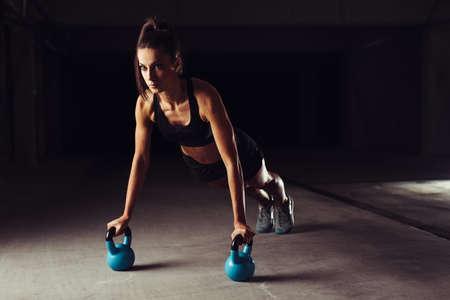 Slim brunette doing push-ups exercises on kettlebells Foto de archivo