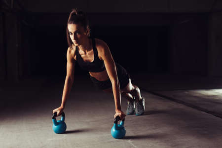 Slim brunette doing push-ups exercises on kettlebells Standard-Bild