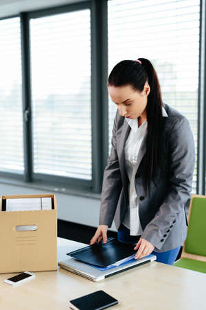 Photo of a female office worker packing her office things after being dismissed