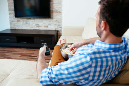 Man sitting on a sofa and holding a remote control Stock Photo