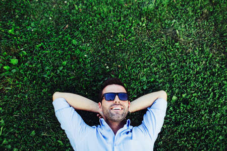 Portrait of a young happy man relaxing on the grass with his hands under the head Stock Photo