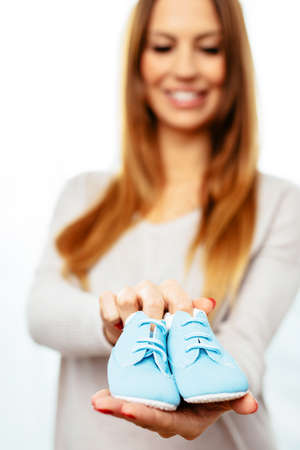 Happy pregnant woman with a pair of baby boots in her hands Standard-Bild