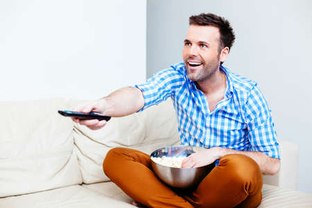 Smiling man watching TV on a sofa with a bowl of popcorn Stock Photo