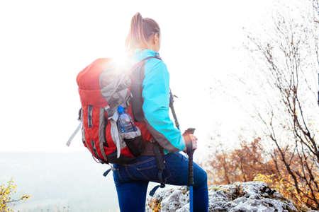 Female hiker climbing with poles Foto de archivo
