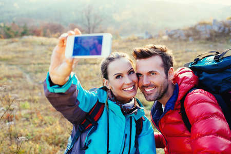 Young smiling couple of hikers taking a selfie