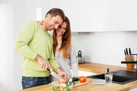 Happy pregnant couple preparing some food together