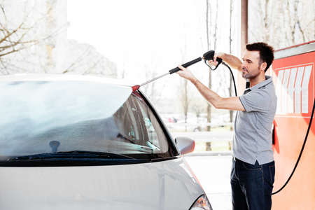 Young man cleaning his car with a jet sprayer