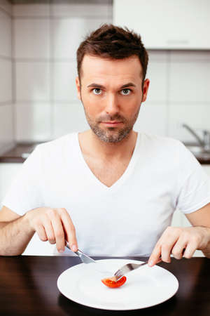 Unhappy man on diet eating a tiny portion of food