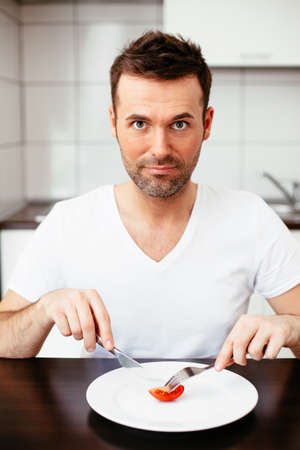 Unhappy man on diet cutting a piece of tomato Stock Photo