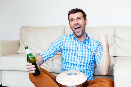 Football fan watching a game on tv and supporting Stock Photo
